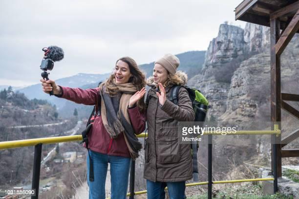 weibliches paar reisende vlogs hoch in den bergen - video call stock-fotos und bilder
