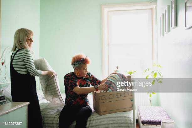 female couple unpacking boxes in new home - human relationship stock pictures, royalty-free photos & images