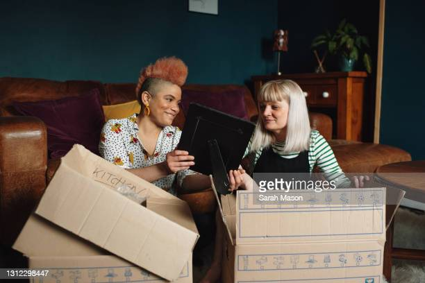 female couple unpacking boxes in new home - couple relationship stock pictures, royalty-free photos & images