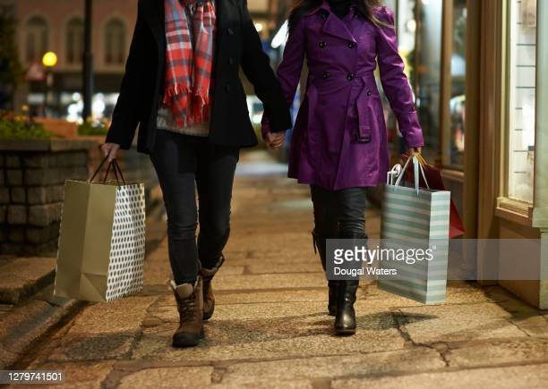female couple walk holding hands and christmas shopping in city. - shop stock pictures, royalty-free photos & images
