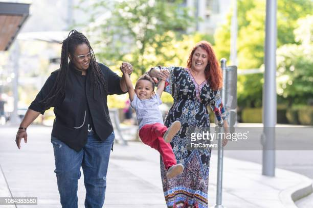 female couple walking with their son - black civil rights stock pictures, royalty-free photos & images