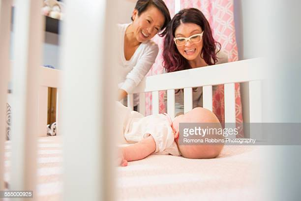 Female couple watching tired baby daughter in crib