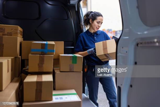 female courier checking the parcel for delivery - 積荷を降ろす ストックフォトと画像