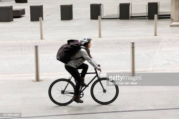 female courier cycles in city street. - bicycle stock pictures, royalty-free photos & images