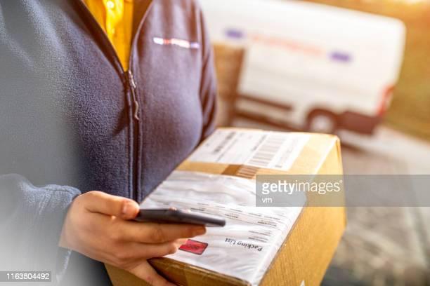 weibliche kurier hält smartphone für die unterschrift - autographs stock-fotos und bilder