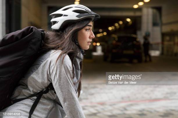 female courier is cycling to delivery destination. - commuter stock pictures, royalty-free photos & images