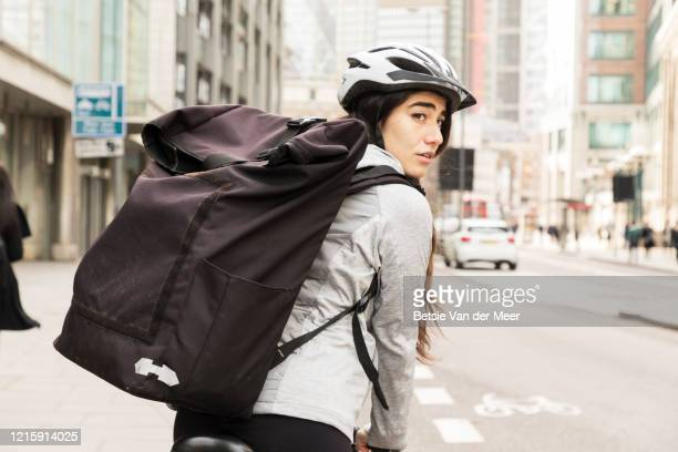 female courier looks over shoulder, while cycling with delivery bag. - looking over shoulder stock pictures, royalty-free photos & images