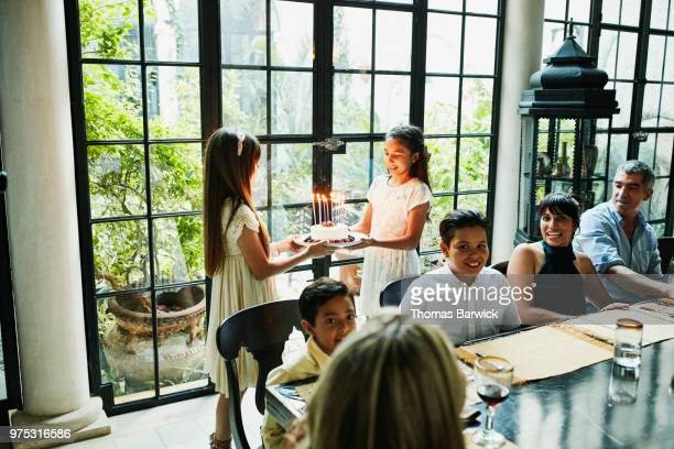 Female cousins bringing birthday cake with candles to dinner table during family birthday party