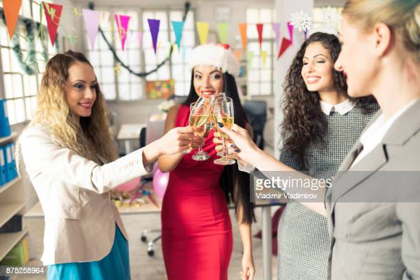 Female coworkers celebrating New Year at workplace