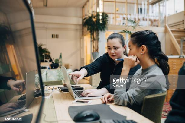 female coworkers discussing coding on laptop while sitting in office - creative occupation stock pictures, royalty-free photos & images