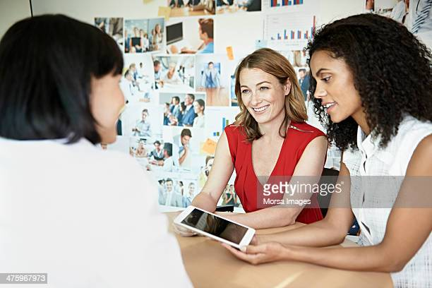 Female coworkers discussing ideas on tablet