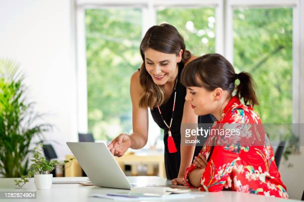 female coworkers discussing in the creative office - fashionable stock pictures, royalty-free photos & images