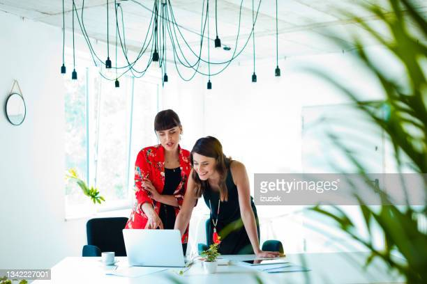 female coworkers discussing in the creative office - coworker stock pictures, royalty-free photos & images