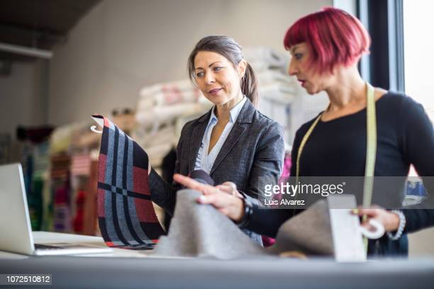 female coworkers discussing over fabric at workshop - fashion designer stock photos and pictures