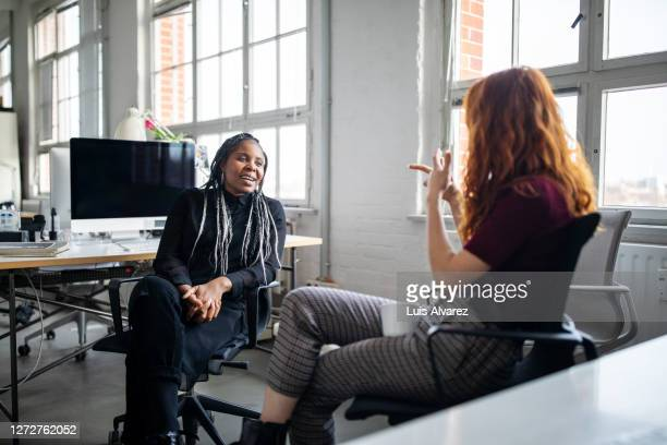 female coworkers discussing work at their desk - long hair stock pictures, royalty-free photos & images