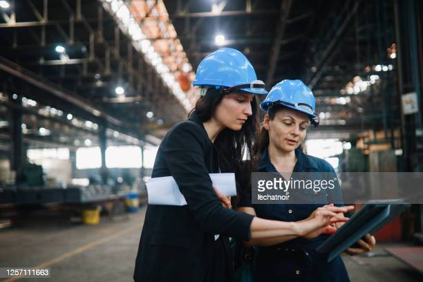 female coworkers in stem doing work on a digital tablet - headwear stock pictures, royalty-free photos & images