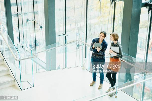female coworkers looking at project data on digital tablet while standing on stairs in office - employee engagement stock pictures, royalty-free photos & images