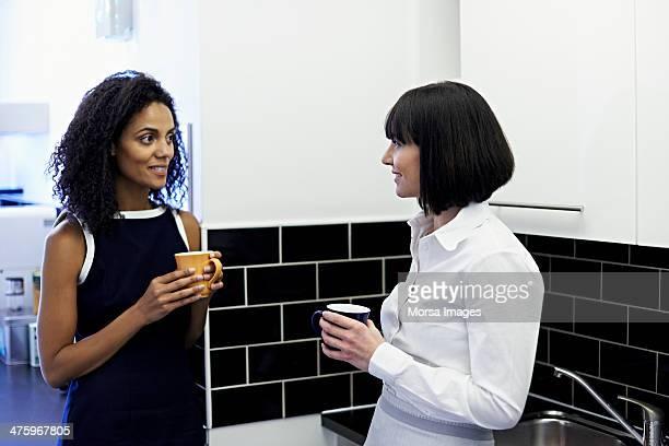 female coworkers on coffee break - capelli neri foto e immagini stock
