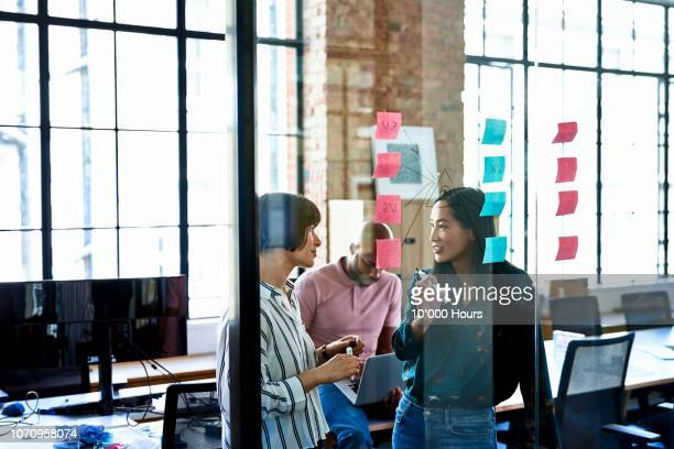 female coworkers problem solving in modern office - joining the dots stock pictures, royalty-free photos & images