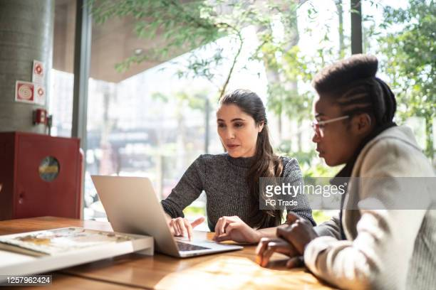 female coworkers using laptop on a meeting - business plan stock pictures, royalty-free photos & images