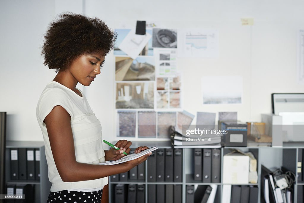 Female creative taking notes on paper : Stock Photo
