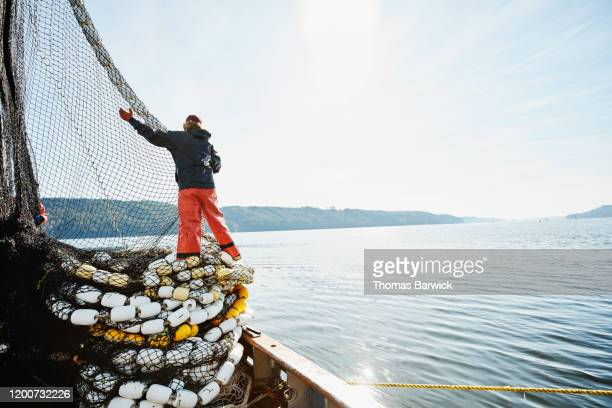 female crew member of fishing boat stacking net on deck while fishing for salmon - fishing industry stock pictures, royalty-free photos & images