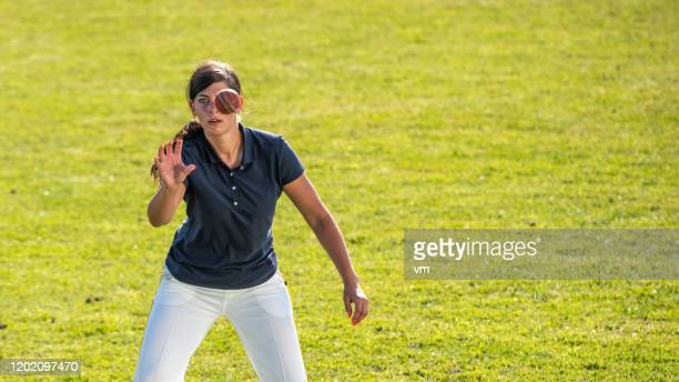 female cricket player catching the ball - sport of cricket stock pictures, royalty-free photos & images