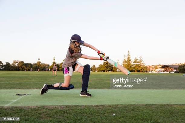 female cricketer batting in evening light - batting stock pictures, royalty-free photos & images