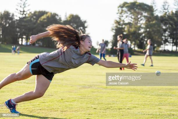 a female cricketer dives to catch the ball - cricket player stock pictures, royalty-free photos & images