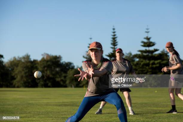 female cricketer prepares to catch the ball on the sports field - women cricket stock pictures, royalty-free photos & images