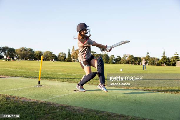 a female crickets bats on a sports field in the evening light - women cricket stock pictures, royalty-free photos & images