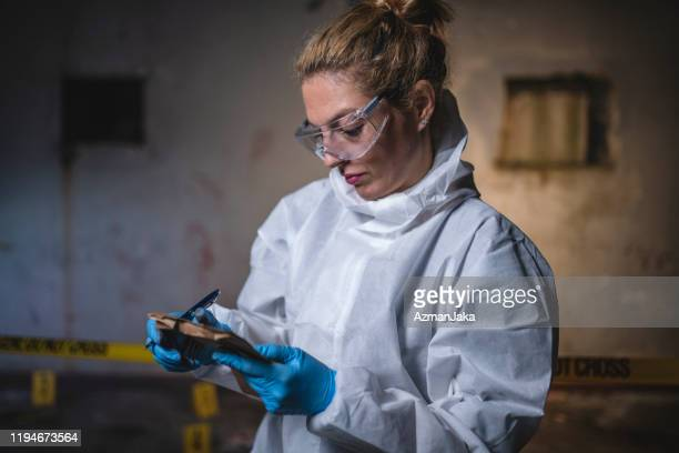 female crime scene investigator making notes - criminal investigation stock pictures, royalty-free photos & images