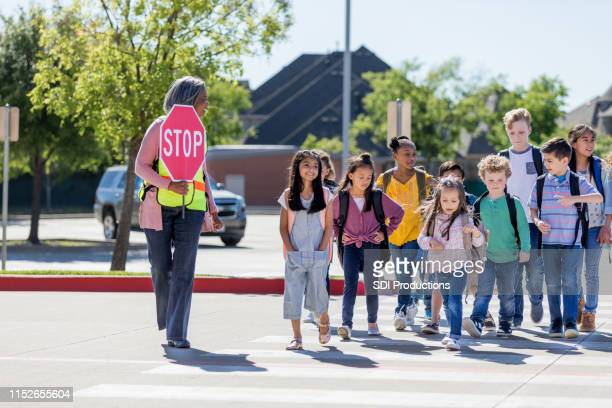 female crossing guard leads children safely across street - crossing stock pictures, royalty-free photos & images