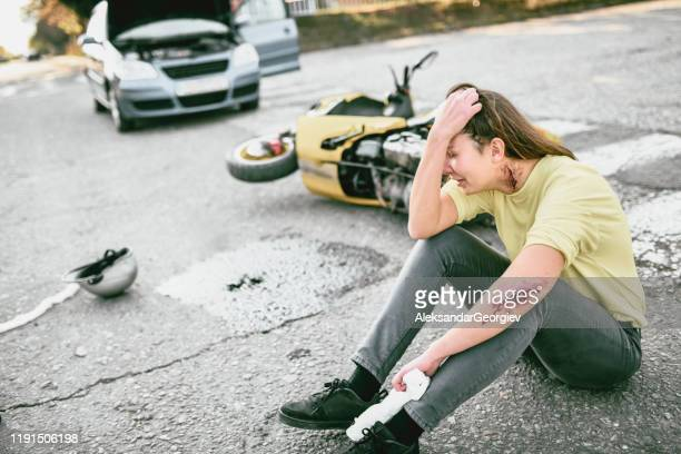 female crying after getting hurt in motorcycle accident - motorcycle accident stock pictures, royalty-free photos & images