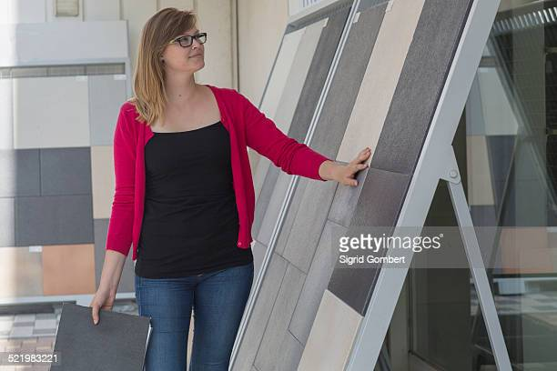 female customer admiring floor tile display in hardware store - sigrid gombert stock pictures, royalty-free photos & images