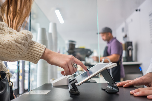 Female Customer Buying Coffee and Placing Signature On Tablet 1138022521