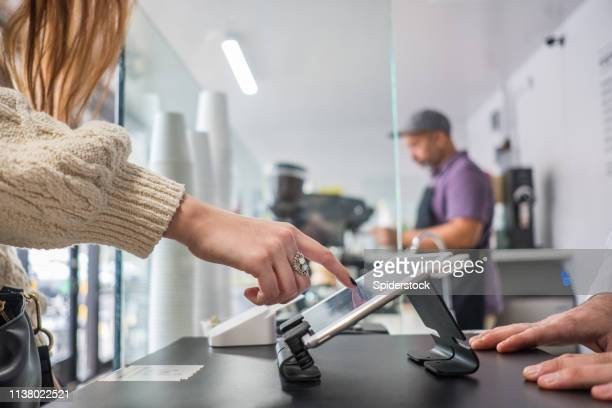 female customer buying coffee and placing signature on tablet - cash register stock pictures, royalty-free photos & images