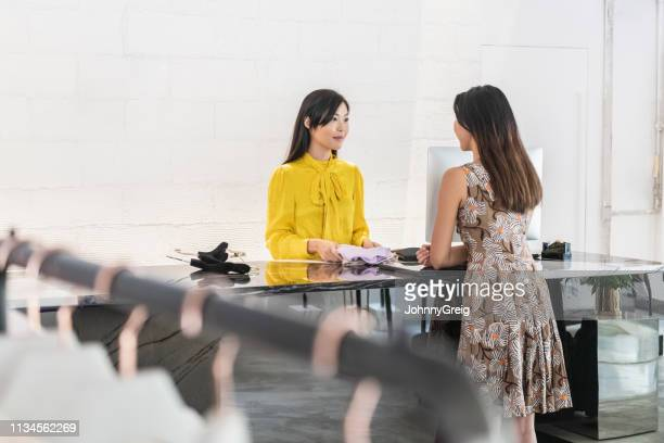 female customer buying garment in modern boutique - returning stock pictures, royalty-free photos & images