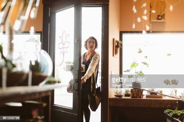 female customer carrying plants in crate while standing at doorway of garden center - entrata foto e immagini stock