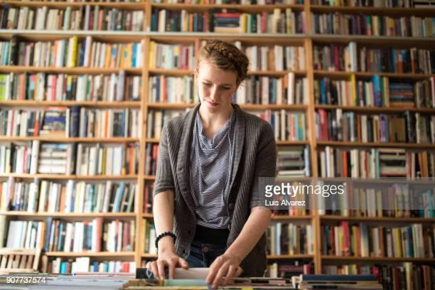 Female customer choosing book against bookshelf