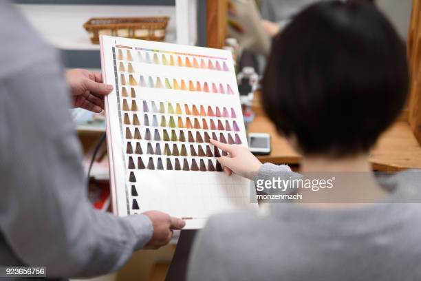 Female customer choosing hair color in hair salon