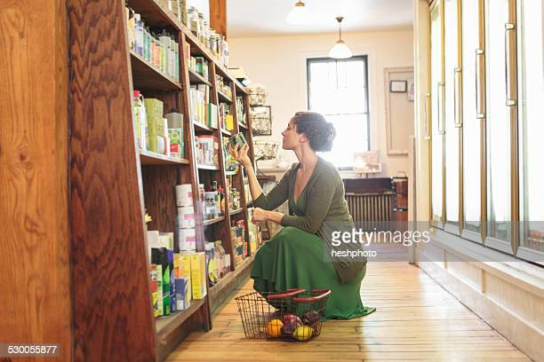 Female customer crouching whilst shopping in country store