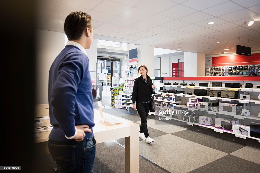 Female customer entering in electronics store : Stock Photo