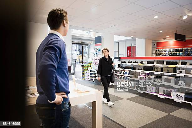 female customer entering in electronics store - electronics store stock photos and pictures