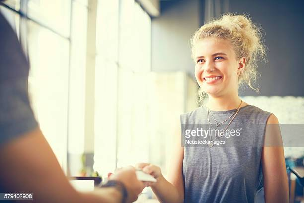 Female customer giving card to cashier in cafe