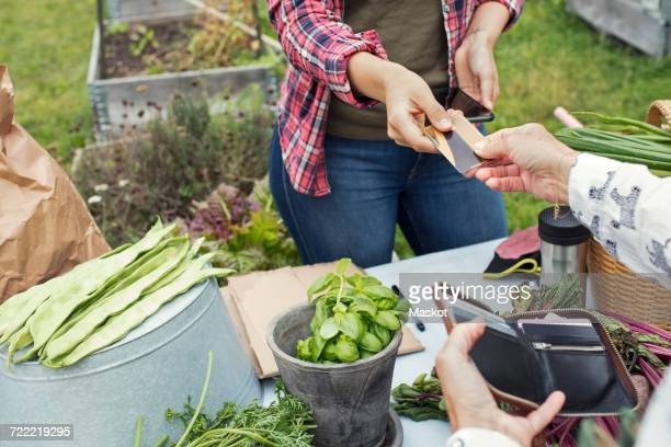 Female customer handing over credit card to woman at vegetable garden