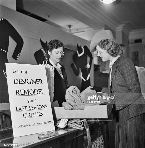 Female customer hands over one of her old dresses to a shop assistant for remodelling into a new style at a counter in the Bourne & Hollingsworth...