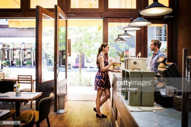 female customer holding coffee cup while talking to owner at counter in cafe - cavan images foto e immagini stock