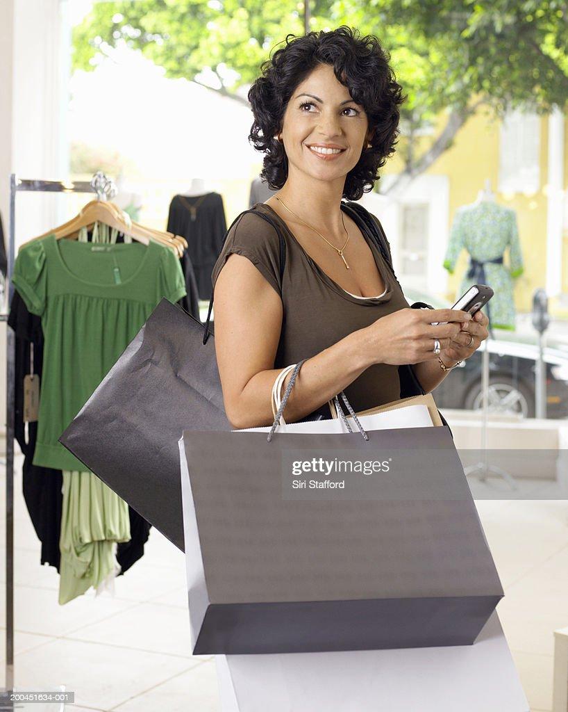 Female customer holding shopping bags and mobile phone : Bildbanksbilder