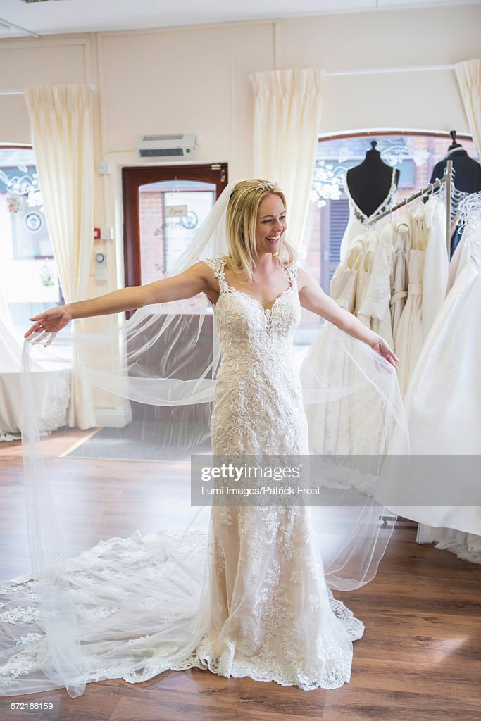 Female Customer In Bridal Shop Trying On Wedding Dress Photo